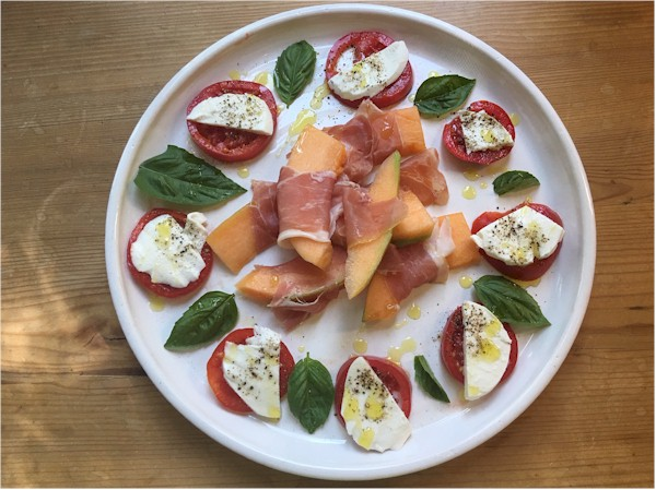 cantaloupe on platter with prosciutto tomatoes mozzarella