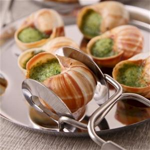 escargot prepared with butter and parsley in shell, held with tongs
