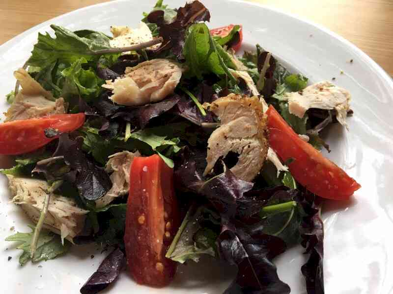 field greens salad with roasted chicken close up