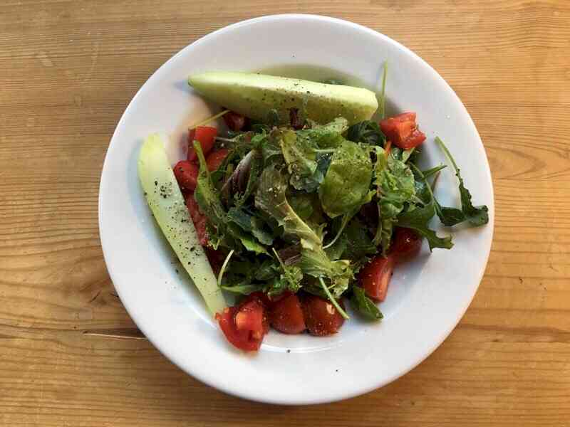 field greens salad on plate with tomatoe and cucumber