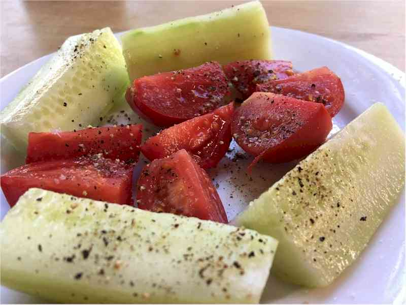 fresh cut up tomatoes and cucumbers on plate