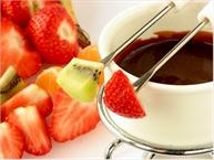 chocolate fondue in pot with fruit