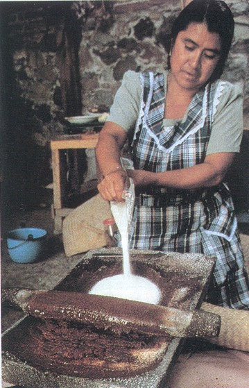 woman making chocolate with metate